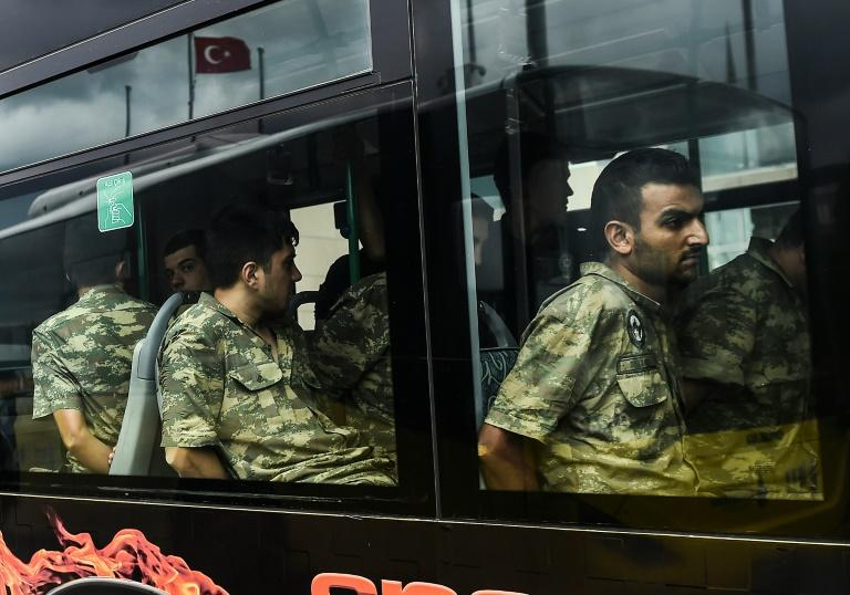 Detained Turkish soldiers who allegedly took part in a military coup arrive in a bus at the courthouse in Istanbul on July 20, 2016, following the military coup attempt of July 15