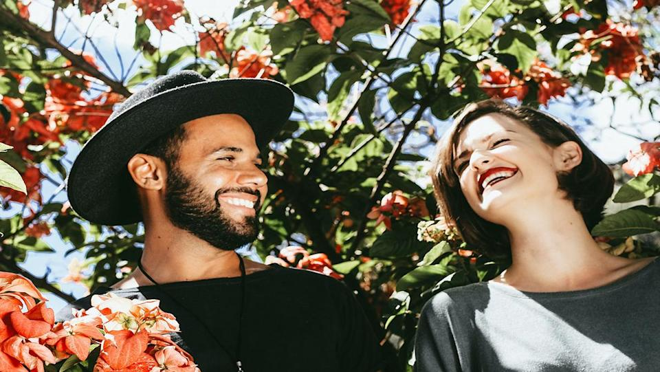 A man and woman laughing in front of green leaves and flowers