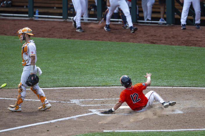 Virginia's Logan Michaels (12) slides home for a run against Tennessee in the seventh inning during a baseball game in the College World Series, Sunday, June 20, 2021, at TD Ameritrade Park in Omaha, Neb. (AP Photo/John Peterson)