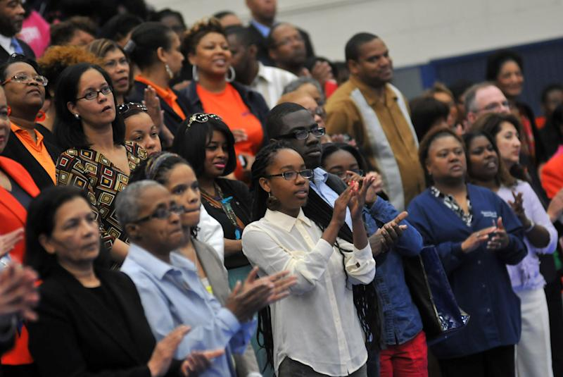 "Audience members applaud during a memorial service at Virginia State University in Chesterfield County, Va. Friday, April 26, 2013 for two students, Jauwan Holmes and Marvell Edmondson, who drowned in the nearby Appomattox River on April 20. Edmonson of Portsmouth and Holmes of Newport News were swept away by the rapids of the Appomattox during what police have described as part of an initiation involving the group ""Men of Honor."" Four men affiliated with the group have been charged with hazing.  VSU has said the little-known group is not sanctioned by VSU. (AP Photo/The Progress-Index, Patrick Kane)"