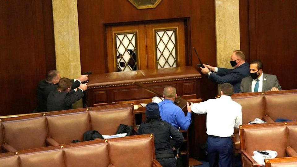 Law enforcement officers point their guns at a door that was vandalised in the House Chamber during a joint session of Congress in Washington DC, 6 January 2021