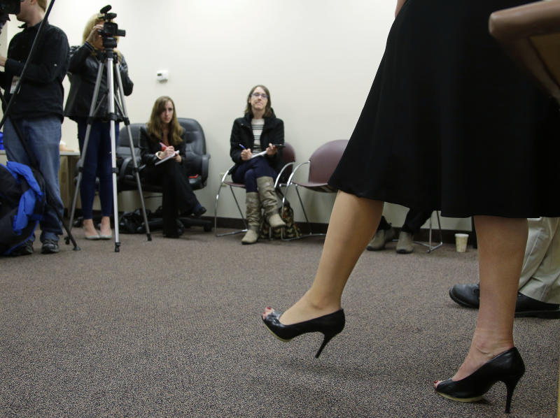 """Heather Abbott of Newport, RI., shows reporter's her new """"high-definition"""" silicon prosthetic leg which now allows her to also wear 4-inch high heels and skirts in Warwick, RI., Thursday, Nov. 7, 2013. Abbott lost her left leg in the April 15, 2013 Boston Marathon bombings. (AP Photo/Stephan Savoia)"""