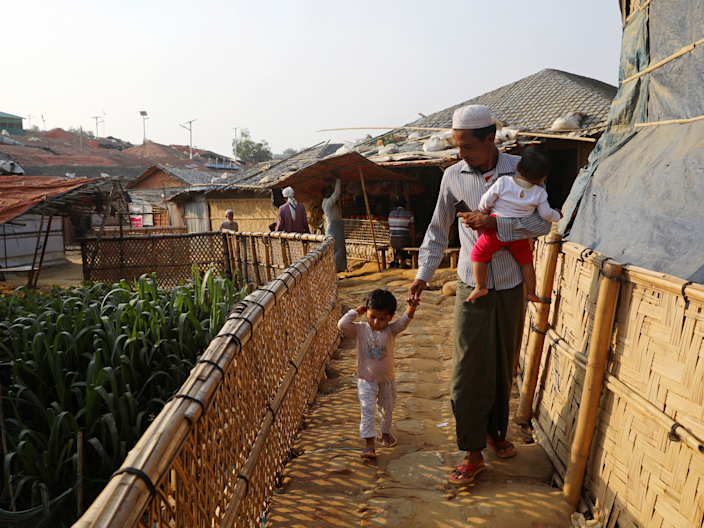 FILE PHOTO: A Rohingya refugee man walks with his children at Balukhali camp in Cox's Bazar, Bangladesh, April 8, 2019. REUTERS/Mohammad Ponir Hossain