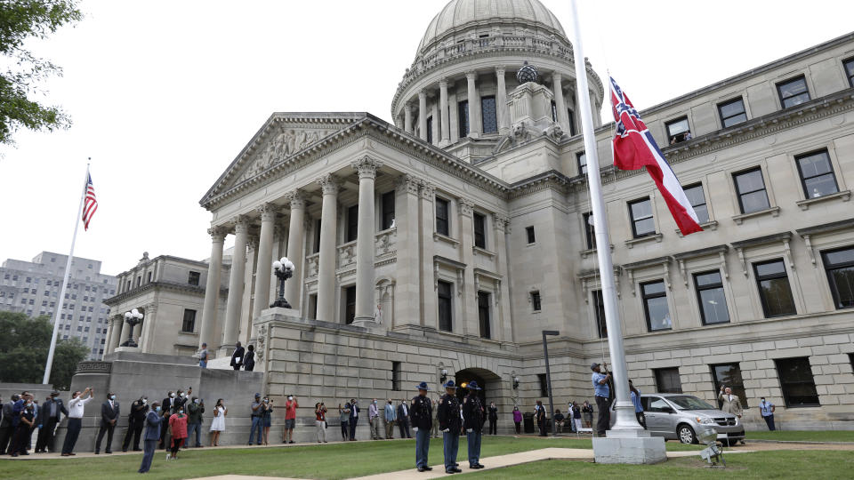 A Mississippi Highway Safety Patrol honor guard stands at attention as the retired Mississippi state flag is raised over the Capitol grounds one final time in Jackson, Miss., Wednesday, July 1, 2020. The banner was the last state flag with the Confederate battle emblem on it. (AP Photo/Rogelio V. Solis)