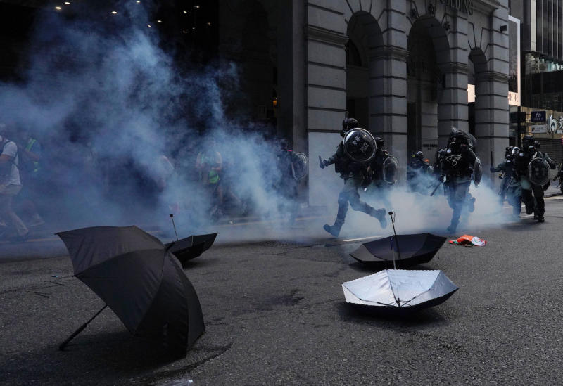 Riot police run past umbrellas abandoned by protesters as tear gas are fired n Hong Kong on Monday, Nov. 11, 2019. A protester was shot by police Monday in a dramatic scene caught on video as demonstrators blocked train lines and roads during the morning commute. (AP Photo/Vincent Yu)