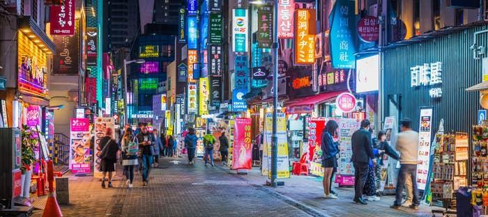 Crowds of shoppers along the pedestrianized streets of Myeong-dong overlooked by the neon lights of stores in the heart of Seoul at night