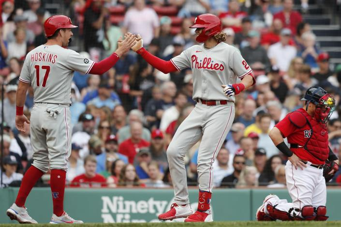 Philadelphia Phillies' Alec Bohm, center, celebrates his two-run home run that also drove in Rhys Hoskins (17) as Boston Red Sox's Christian Vazquez, right, kneels at home plate during the second inning of a baseball game, Saturday, July 10, 2021, in Boston. (AP Photo/Michael Dwyer)