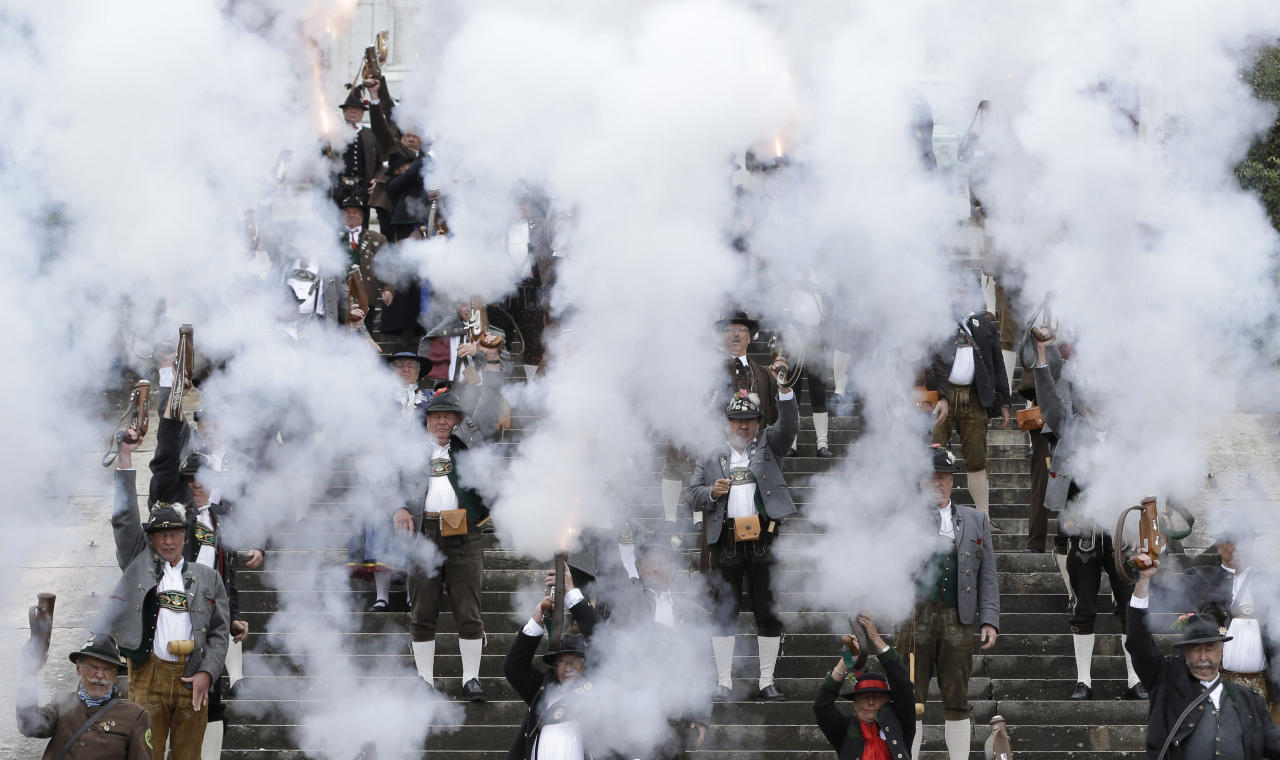 Bavarian riflemen and women in traditional costumes fire their muzzle loaders in Munich, southern Germany, Sunday, Oct. 7, 2012. Members of various shooting clubs of the region met for a salute on the last day of the famous Oktoberfest beer festival. (AP Photo/Matthias Schrader)