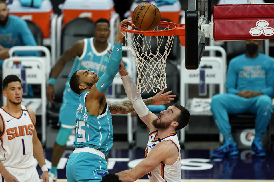 Charlotte Hornets forward P.J. Washington is fouled by Phoenix Suns forward Frank Kaminsky, right, during the first half of an NBA basketball game, Wednesday, Feb. 24, 2021, in Phoenix. (AP Photo/Matt York)