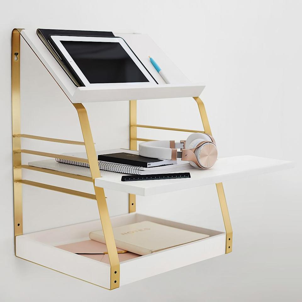 """<h3>PBteen Laddered Standing Desk</h3><br>This nifty workspace mounts to your wall for three tiers of standing office space. <br><br><strong>PBTeen</strong> Laddered Standing Desk Converter, White/Brass, $, available at <a href=""""https://go.skimresources.com/?id=30283X879131&url=https%3A%2F%2Fwww.pbteen.com%2Fproducts%2Fladdered-standing-desk-converter%2F"""" rel=""""nofollow noopener"""" target=""""_blank"""" data-ylk=""""slk:PBTeen"""" class=""""link rapid-noclick-resp"""">PBTeen</a>"""