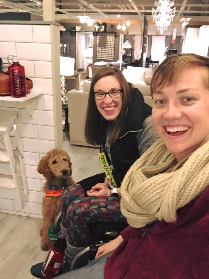 two women sitting in wheelchairs at ikea with one of the women's service dog in the background