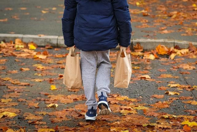 A child collects packed lunch bags