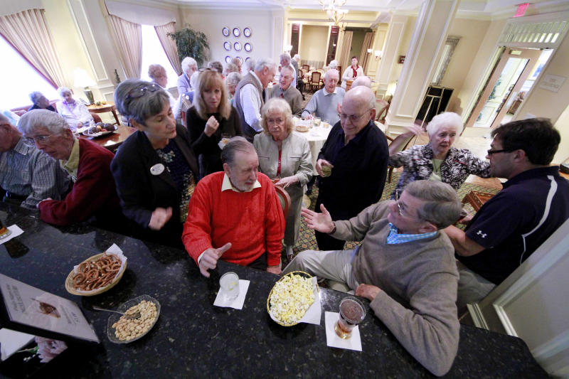 In this photo taken Friday, Oct. 28, 2011, residents from The Village at Penn State, Al Green, center in red, and Jim Scott, right in gray, gather with other residents for a happy hour before dinner in State College, Pa. With many people seeking a retirement that is culturally active and intellectually stimulating, colleges and universities are working to bring retirees to their campuses and towns.    (AP Photo/Gene Puskar)