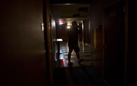 A guest walks toward the lobby of a hotel illuminated by emergency lights following a power outage in Tampa, Florida - Credit: Bloomberg