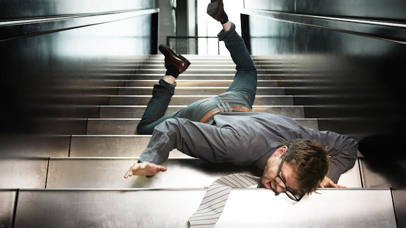 A man in a business suit falling down the stairs.