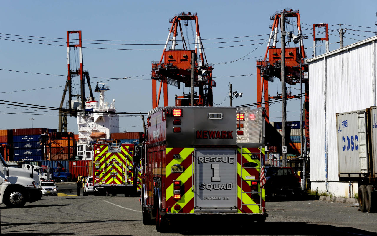 Emergency officials arrive at Port Newark to investigate reports of stowaways in a container on a ship, Wednesday, June 27, 2012, in Newark, N.J. The Coast Guard suspects there are stowaways in a container that was loaded on a ship. Coast Guard spokesman Charles Rowe says a boarding party heard sounds consistent with people coming from the container. The container was loaded aboard The Villa D'Aquarius in India. The manifest says the container was carrying machine parts to be unloaded in Norfolk, Va. (AP Photo/Julio Cortez)