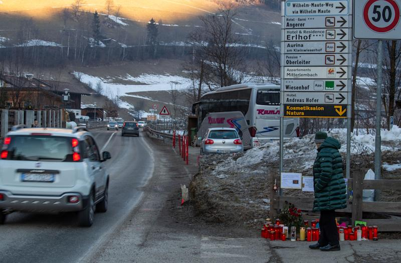 06 January 2020, Italy, Bozen: A woman walks past flowers and candles at the scene of the accident. A car had driven into a group of holidaymakers and killed six young Germans in the process. Photo: Lino Mirgeler/dpa (Photo by Lino Mirgeler/picture alliance via Getty Images)