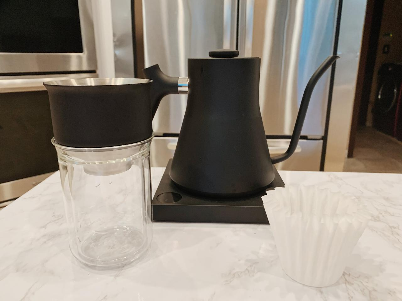 """<p>Lay out all the materials you need to make your pour-over coffee. Apart from ground coffee beans, you'll need a pour-over kettle like this <product href=""""https://fellowproducts.com/products/staggekg?utm_source=google&amp;utm_medium=awareness&amp;utm_campaign=search_nonbrand&amp;gclid=Cj0KCQjw8fr7BRDSARIsAK0Qqr4wvKptPjlA8m-kZ7lEAfGDsNF5nU8Jy32tSY7pjEdSGjOERy6Vbf8aAiH2EALw_wcB"""" target=""""_blank"""" class=""""ga-track"""" data-ga-category=""""internal click"""" data-ga-label=""""https://fellowproducts.com/products/staggekg?utm_source=google&amp;utm_medium=awareness&amp;utm_campaign=search_nonbrand&amp;gclid=Cj0KCQjw8fr7BRDSARIsAK0Qqr4wvKptPjlA8m-kZ7lEAfGDsNF5nU8Jy32tSY7pjEdSGjOERy6Vbf8aAiH2EALw_wcB"""" data-ga-action=""""body text link"""">Fellow Stagg EKG Electric Pour-Over Kettle</product> ($149) and a pour-over set that comes with a dripper, glass, and filters like this <product href=""""https://fellowproducts.com/products/stagg-x-single-set"""" target=""""_blank"""" class=""""ga-track"""" data-ga-category=""""internal click"""" data-ga-label=""""https://fellowproducts.com/products/stagg-x-single-set"""" data-ga-action=""""body text link"""">Fellow Stagg [X] Pour-Over Set</product> ($69). You could also buy the dripper, glass, and filters separately. Now you're ready to get pouring!</p>"""