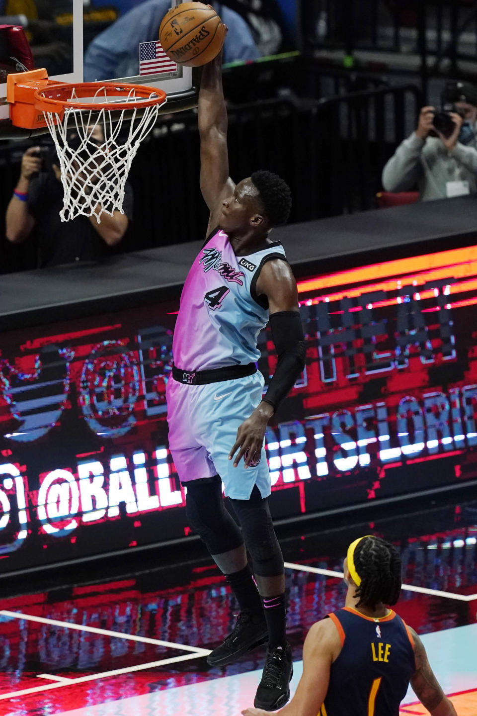 Miami Heat guard Victor Oladipo (4) dunks in front of Golden State Warriors guard Damion Lee (1) during the first half of an NBA basketball game Thursday, April 1, 2021, in Miami. (AP Photo/Marta Lavandier)
