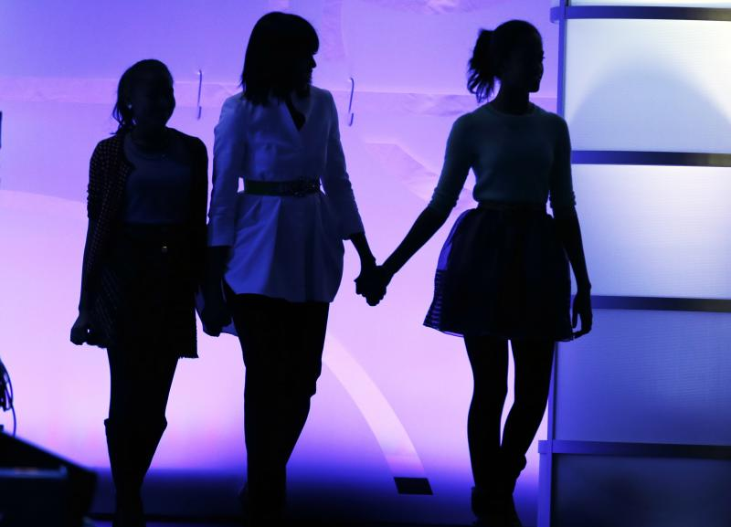 """First lady Michelle Obama, center, and daughters Sasha, left, and Malia, right, walk on stage during the Kids' Inaugural: Our Children. Our Future."""" event in Washington, Saturday, Jan. 19, 2013, as part of the 57th Inauguration weekend of events. (AP Photo/Frank Franklin II)"""