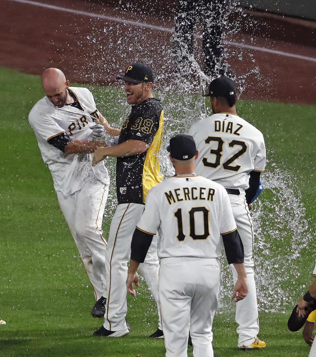 Pittsburgh Pirates' Jacob Stallings, left, is held by Chad Kuhl (39) as Elias Diaz (32) showers him while celebrating after hitting a walkoff single off Kansas City Royals relief pitcher Ben Lively in the bottom of the ninth of a baseball game in Pittsburgh, Monday, Sept. 17, 2018. (AP Photo/Gene J. Puskar)