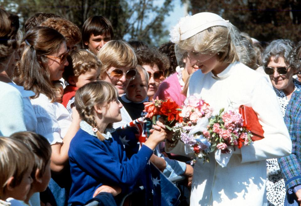 LAUNCESTON, AUSTRALIA - MARCH 31: Diana, Princess of Wales, wearing a cream gabardine suit designed by Jasper Conran with a matching hat with flowers and a veil designed by John Boyd, speaks to well-wishers during a walkabout in Launceston on March 31, 1983 in Tasmania, Australia. (Photo by Anwar Hussein/Getty Images)