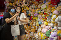 A woman wearing a face mask to protect against the coronavirus poses for a selfie in front of a wall of stuffed animals at an arcade in Beijing, Saturday, Aug. 1, 2020. China reported a more than 50% drop in new cases of COVID-19 on Saturday in a possible sign that its latest major outbreak in the northwestern region of Xinjiang may be waning. (AP Photo/Mark Schiefelbein)