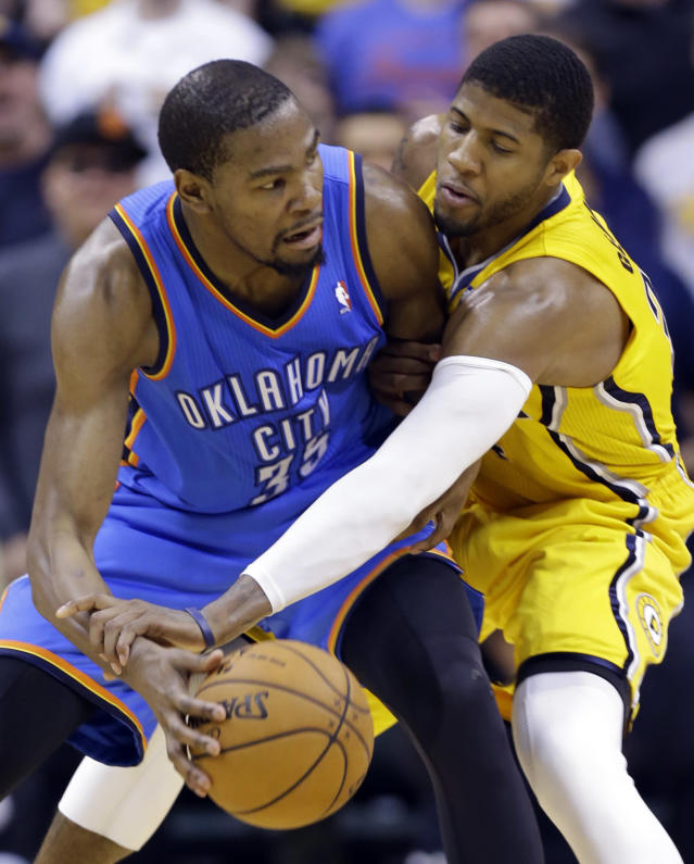 Indiana Pacers forward Paul George, right, attempts to knock the ball away from Oklahoma City Thunder forward Kevin Durant in the second half of an NBA basketball game in Indianapolis, Sunday, April 13, 2014. The Pacers defeated the Thunder 102-97. (AP Photo/Michael Conroy)