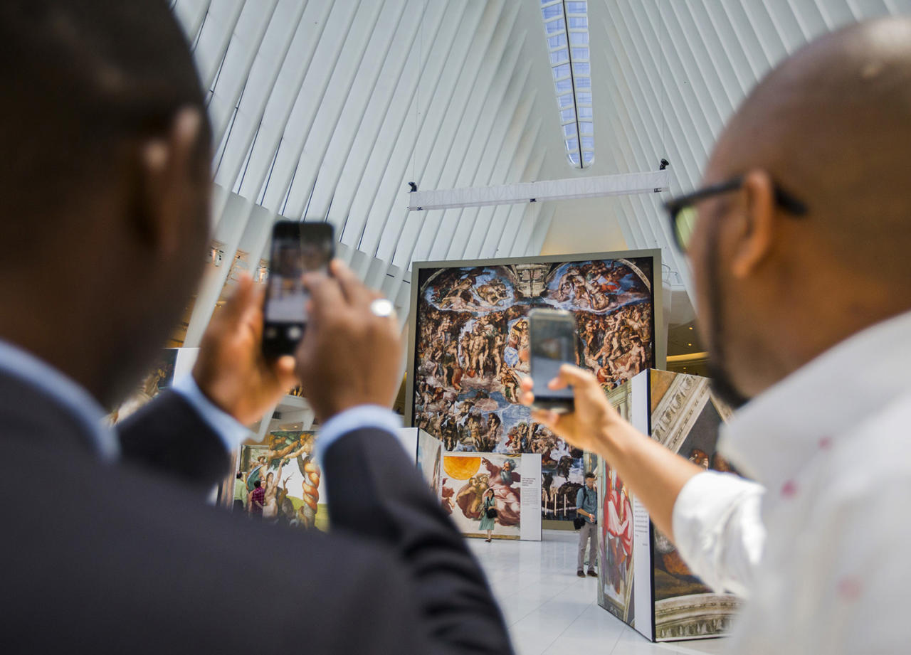 "<p>Passersby take photos of the 'Up Close: Michelangelo's Sistine Chapel' re-creation exhibit at the Oculus at Westfield World Trade Center in New York. The exhibit features 34 reproductions, including ""The Creation of Adam"" and ""The Last Judgement."" (AP Photo/Michael Noble Jr.) </p>"