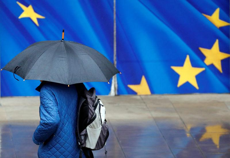 A man with an umbrella walks past the EU Commission headquarters in Brussels