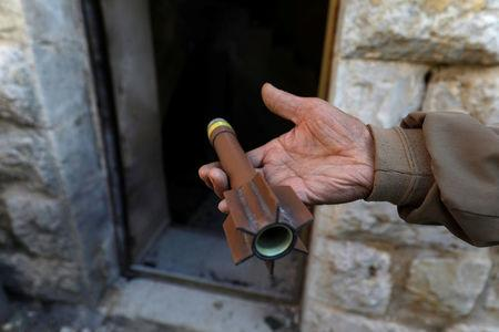Man shows ammunition outside a house where a Palestinian gunman was killed by Israeli forcesin the Israeli-occupied West Bank