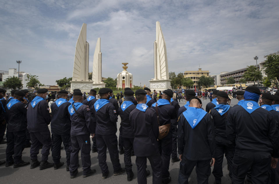 Police stand guard as anti-government protesters rally near the Democracy Monument in Bangkok, Thailand, Wednesday, Oct. 14, 2020. Anti-government protesters began gathering Wednesday for a planned rally at Bangkok's Democracy Monument being held on the anniversary of a 1973 popular uprising that led to the ousting of a military dictatorship, amid a heavy police presence and fear of clashes with political opponents. (AP Photo/Sakchai Lalit)