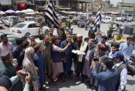 Leaders of the Pakistani religious group Jamiat Ulema-e Islam Nazryati party distribute sweets among people to celebrate the Taliban's victory in Afghanistan, at a market, in Quetta, Pakistan, Tuesday, Aug. 31, 2021. (AP Photo/Arshad Butt)