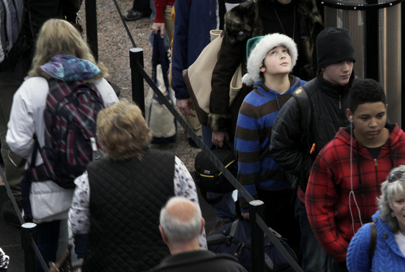 While wearing a green Santa hat, Colter Schoer, 10, of Denver,  joins the holiday crowd in the long but swiftly moving security line at Denver International Airport, Tuesday, Dec. 21, 2010. (AP Photo/Barry Gutierrez)