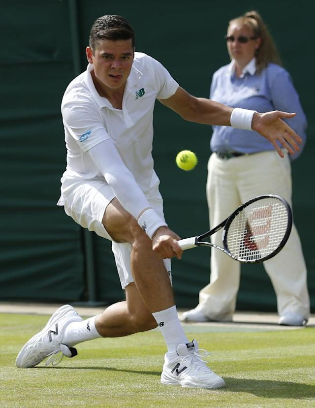 Milos Raonic of Canada hits a return to Matthew Ebden of Australia during their first round match at the All England Lawn Tennis Championships in Wimbledon, London, Tuesday, June 24, 2014. (AP Photo/Ben Curtis)
