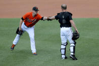 Baltimore Orioles non-roster invitee pitcher Thomas Eshelman, left, gives a fist bump to non-roster invitee catcher Bryan Holaday after working out during baseball training camp, Friday, July 3, 2020, in Baltimore. (AP Photo/Julio Cortez)