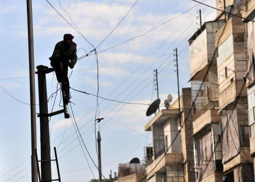 A Syrian man attempts to fix the electricity cables in the northern city of Aleppo on February 14, 2013