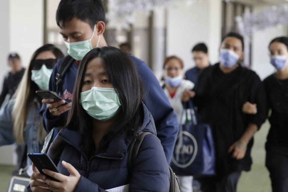 Passengers wear masks as they arrive at Manila's international airport, Philippines, Thursday, Jan. 23, 2020. The government is closely monitoring arrival of passengers as a new coronavirus outbreak in Wuhan, China has infected hundreds and caused deaths in that area. (AP Photo/Aaron Favila)