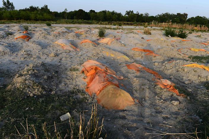 <p>Bodies of suspected Covid-19  victims are seen partially buried in the sand near a cremation ground on the banks of the Ganges</p> (AFP via Getty Images)