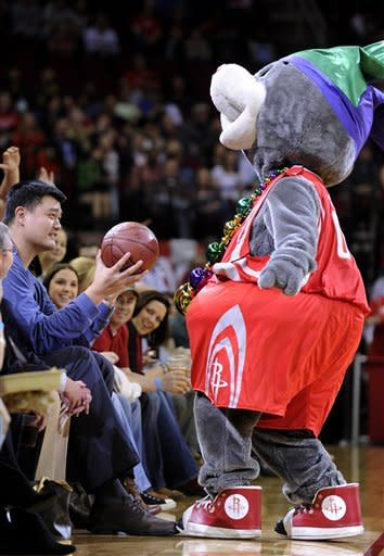 Former Houston Rockets player Yao Ming, left, holds out a basketball from team mascot Clutch during a time out in the first half of an NBA basketball game against the Portland Trail Blazers, Friday, Feb. 8, 2013, in Houston. (AP Photo/Pat Sullivan)