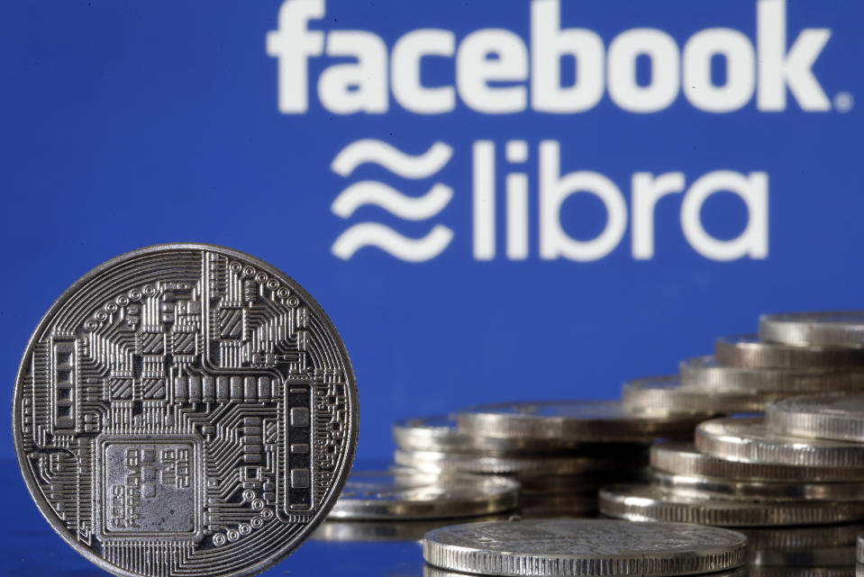 """PARIS, FRANCE - JUNE 24: In this photo illustration, a visual representation of a digital cryptocurrency coin sits on display in front of Libra and Facebook logos on June 24, 2019 in Paris, France. Since the announcement of its creation a few days ago, the virtual currency of Facebook Libra fascinates as much as it worries. Thus, a few days after the announcement of the arrival of the social network in the sector, the Bank for International Settlements (BIS) considers that the incursion of major technologies into financial activity presents """"new and complex compromises between financial stability , competition and data protection """". (Photo by Chesnot/Getty Images)"""