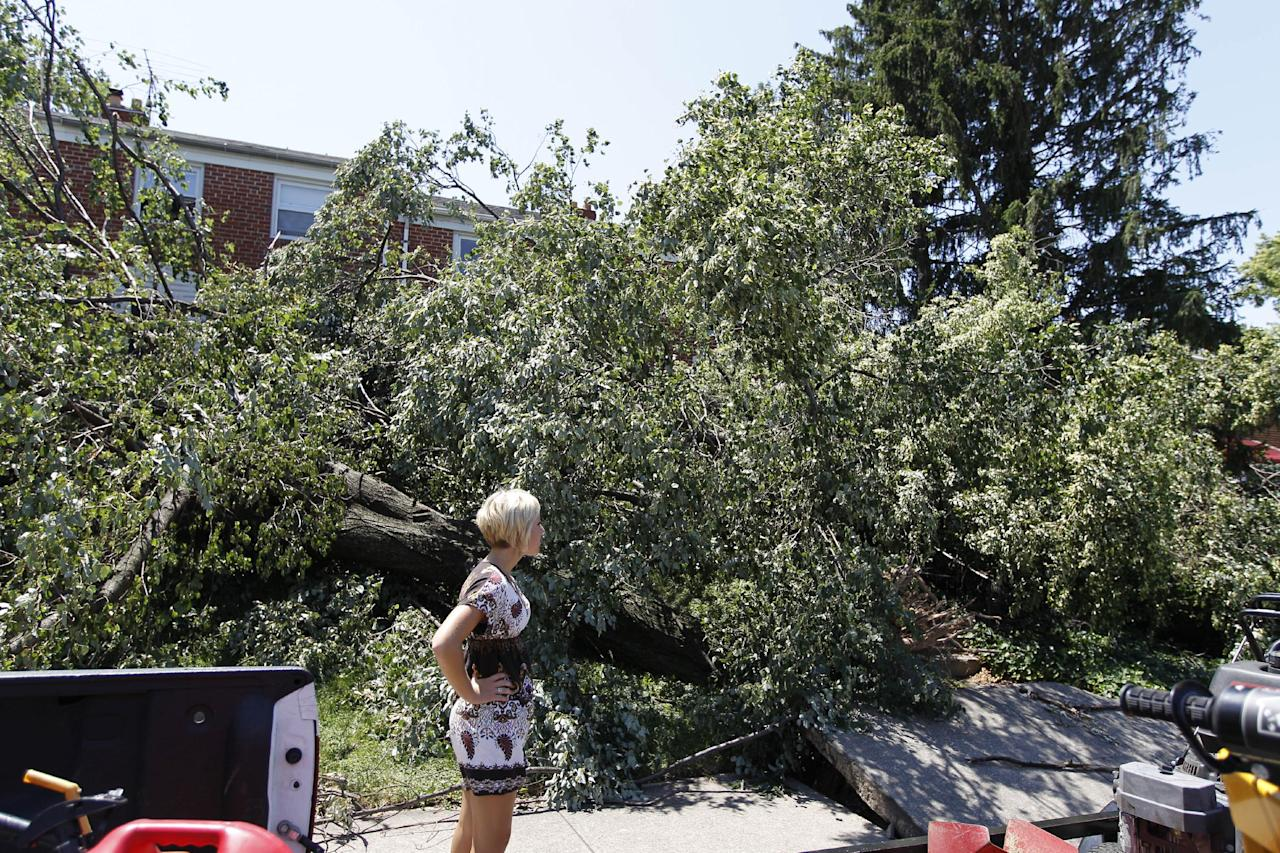 A pedestrian takes a look at downed trees blocking the entrance of a house in Baltimore on Monday July 2, 2012, after a severe storm swept through the region late Friday. Power outages left many to contend with stifling homes and spoiled food over the weekend as temperatures approached or exceeded 100 degrees.(AP Photo/Jose Luis Magana)