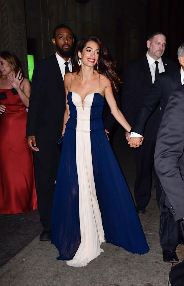 <p>For The United Nations Correspondents Association Awards, Amal dressed in a £5,090 colour-block dress by J.Mendel accessorised with loose waves and a miniature handbag. <em>[Photo: Getty]</em> </p>