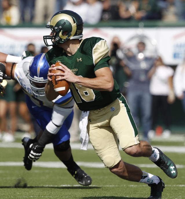 Colorado State quarterback Garrett Grayson, front, eludes San Jose State nose tackle Nate Falo in the first quarter of an NCAA college football game in Fort Collins, Colo., on Saturday, Oct. 12, 2013. (AP Photo/David Zalubowski)