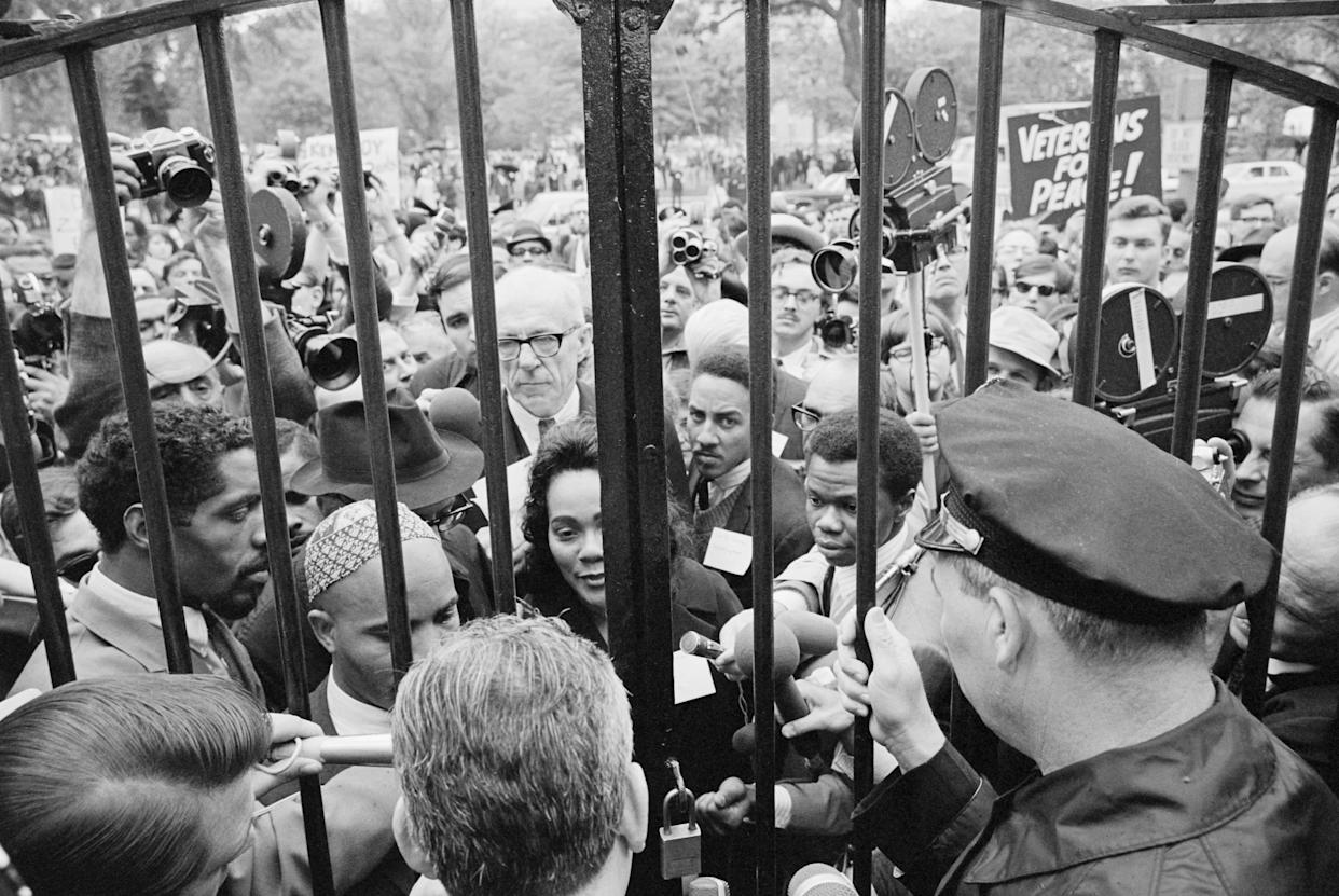Demonstrators representing the 'Mobilization to End the War in Vietnam,' jam to the barred main gate of the White House today in Washington, D.C. on May 17, 1967. The group was led by Mrs. Martin Luther King (center) and Dr. Benjamin Spock (glasses, directly behind Mrs. King), who read a statement denouncing the Administration policies in Vietnam.