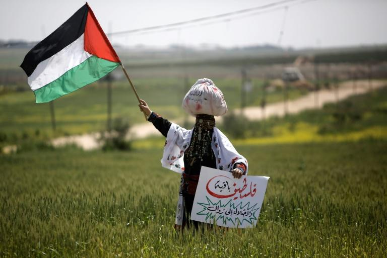 A Palestinian woman waves her national flag to mark Land Day near the Israel-Gaza border as mass rallies planned to commemorate the event were cancelled amid concerns about the spread of coronavirus