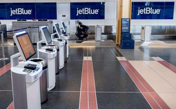 PHOTO: A JetBlue employee waits for passengers at an empty check-in counter at Ronald Reagan Washington National Airport in Arlington, Va., on May 12, 2020. (Andrew Caballero-Reynolds/AFP via Getty Images)
