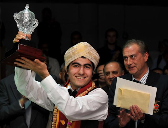 Iran's Hossein Vafaei Ayouri (L) poses with the trophy while wearing the traditional 'Mysooru Peta' (Mysore Turban) after winning the IBSF World Snooker Championship in Bangalore on December 03, 2011. Hossein Lee Walker of Wales by 10 frames to nine. AFP PHOTO/Manjunath KIRAN (Photo credit should read Manjunath Kiran/AFP/Getty Images)