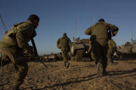 Israeli soldiers run for cover under armored vehicles as a siren sounds warning of incoming rockets fired from Gaza strip in a staging area near the Israeli-Gaza border southern Israel, Saturday, May 15, 2021. (AP Photo/Maya Alleruzzo)a