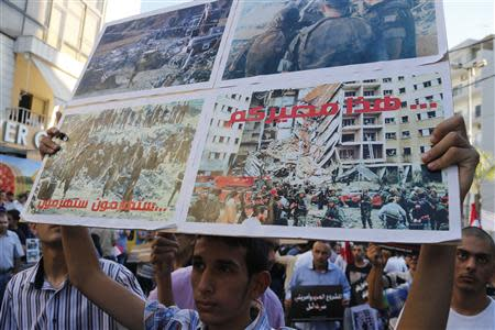 """An activist holds up a placard, which reads: """"You will be defeated. This is your destiny"""", during a sit-in near the U.S. embassy in Awkar, north of Beirut, against potential U.S. strikes on Syria September 6, 2013. U.S. officials ordered non-emergency personnel and their family members out of Lebanon on Friday """"due to threats,"""" the U.S. embassy in Beirut said in statement. The picture on the bottom right of the placard shows a scene from the 1983 suicide bombing of the U.S. embassy in Beirut. REUTERS/Mohamed Azakir"""